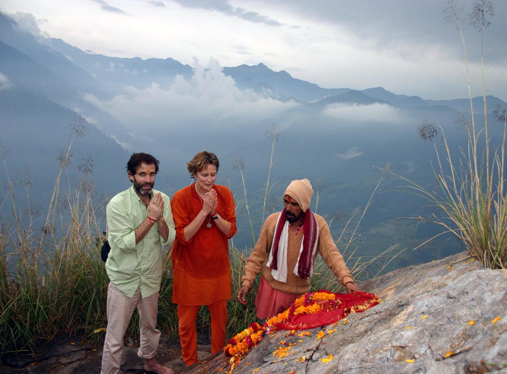 Two westerners stand next to the Kali Murthi. The Priest who lives at the top of the mountain gestures to the murthi. The surrounding mountains frame the image.
