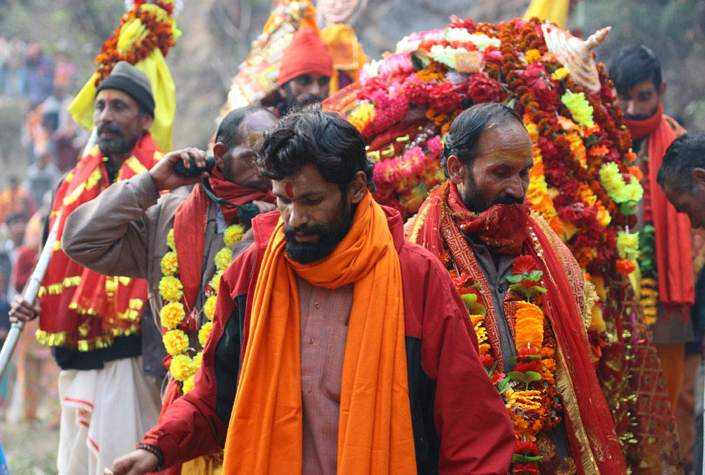 Brightly dressed men with red robes and red/yellow flower garlands walk in a procession.