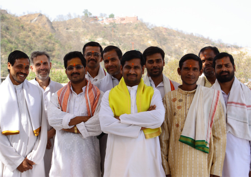 Ganesh stands to the left side of a group of ten smiling men. They are all wearing white robes (kortas and Dhoti's). The mountains surrounding haridwar frame them.