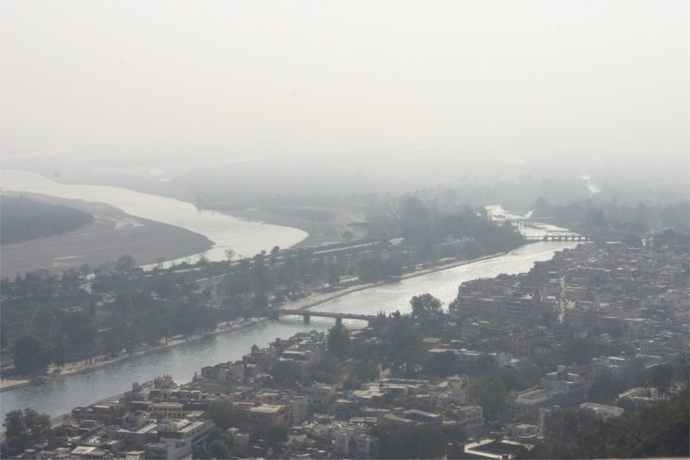 Haridwar as seen from Mansa Devi. The river cuts a swathe through the mass of buildings that is haridwar. The sky is dusty white