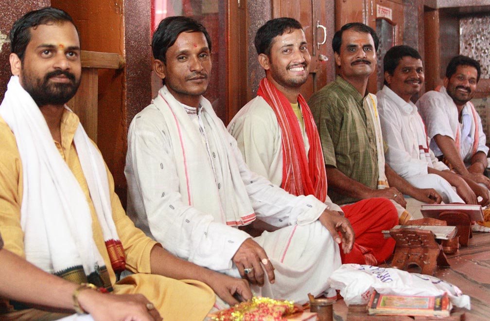 The pandits sit in lotus positions lined left to right all smiling at the camera.