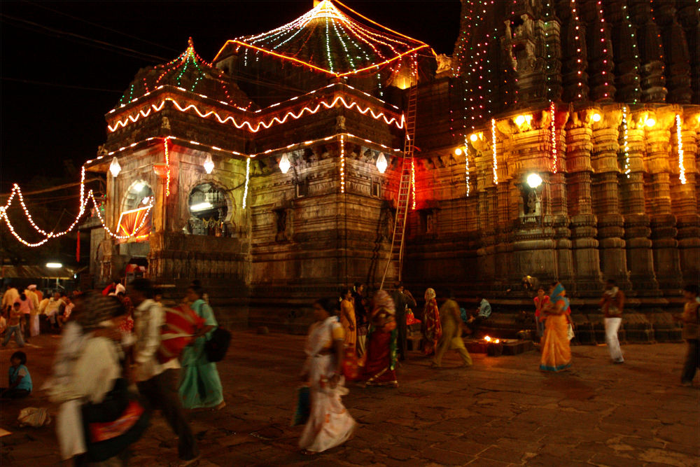The temple is adorned with lights that flicker and cycle through many colours. Pictured are fairy lights which line the walls of the stone exterior.