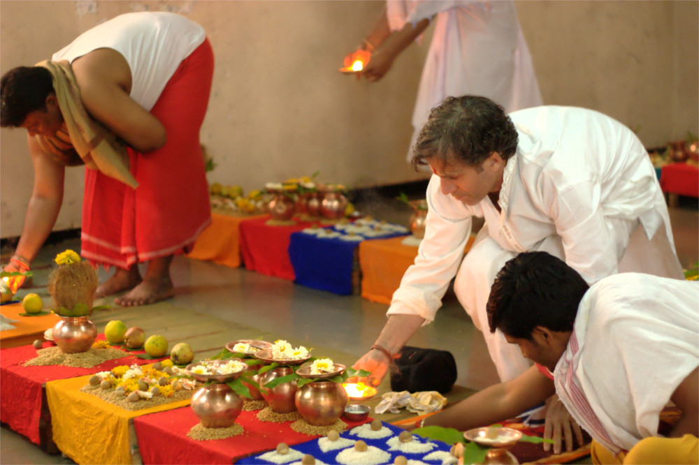Ganesh and several pandits bend over to attend to the offerings (plates of food and flowers) that are part of the ceremony