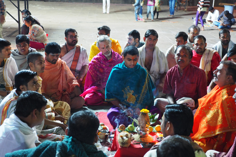 Ganesh and many pandits sit and meditate while the two young pandits lead the ceremony