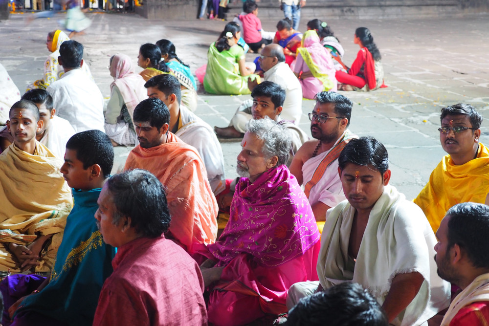 Ganesh in bright pink robes sitting amongst the pandits and they complete the ceremony