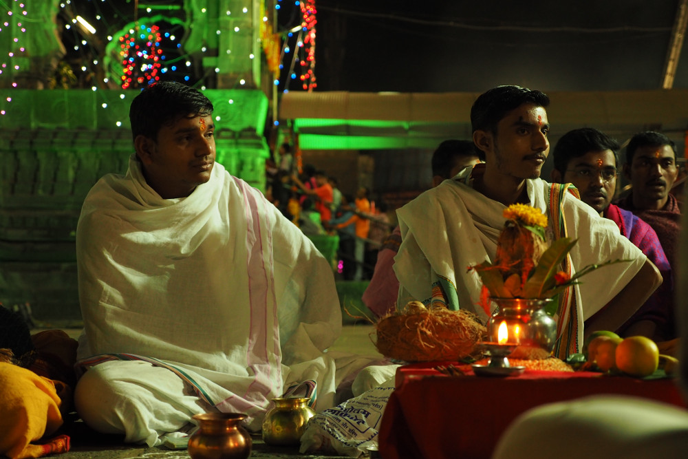 Two pandits sit and Chant during the pooja
