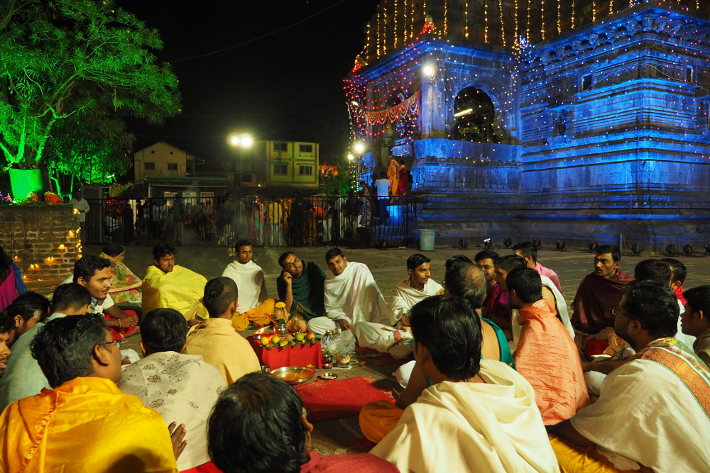 Pandits completing the shiva ratri with the temples in the background