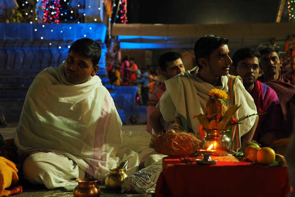 Two young men in white robes sitting cross-legged leading the Pooja